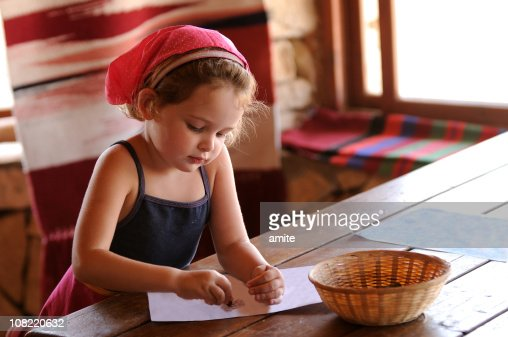 Little Girl Sitting At Table Coloring With Crayons Stock Photo