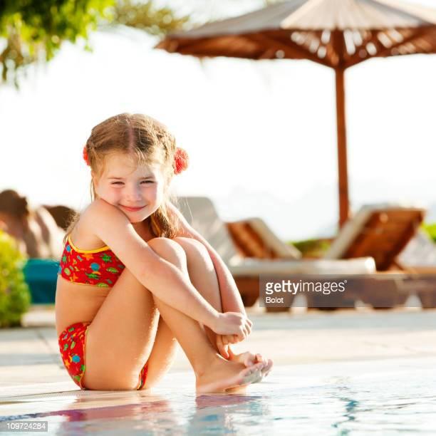 Petite fille de détente près de bord de la piscine le jour ensoleillé
