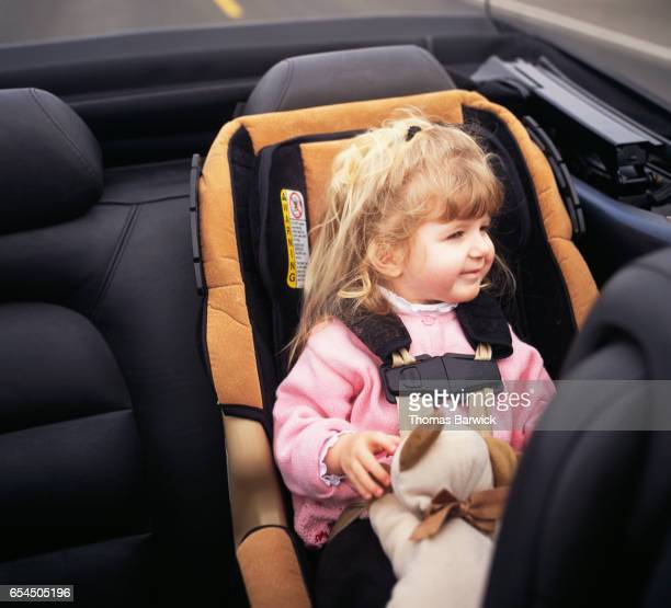 Little Girl Sitting in Backseat of Convertible