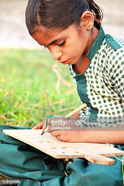 Little girl sitting in the field & writing