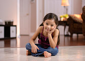 Little girl sitting in the living room, smiling
