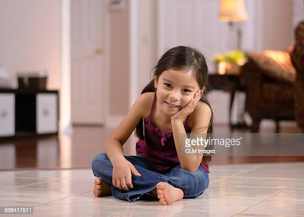 Little girl sitting in the living room, smiling