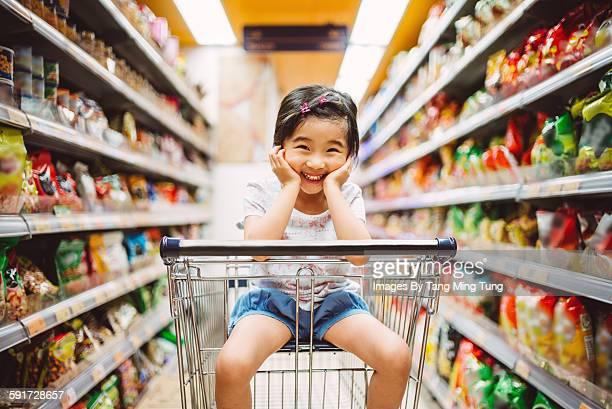 Little girl sitting in trolley in grocery store