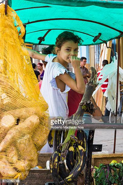 Little girl sitting inside vegetable vendor cart at local market street Camaguey is a Unesco World Heritage Site