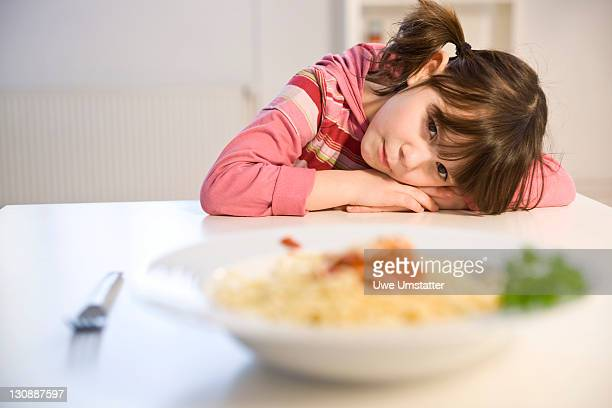 Little girl sitting listlessly in front of a plate of spaghetti