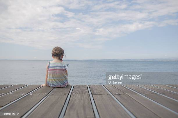 Little girl sitting on a landing stage