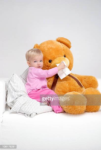 Little Girl Sitting on Bed and Wiping Teddy Bear's Nose