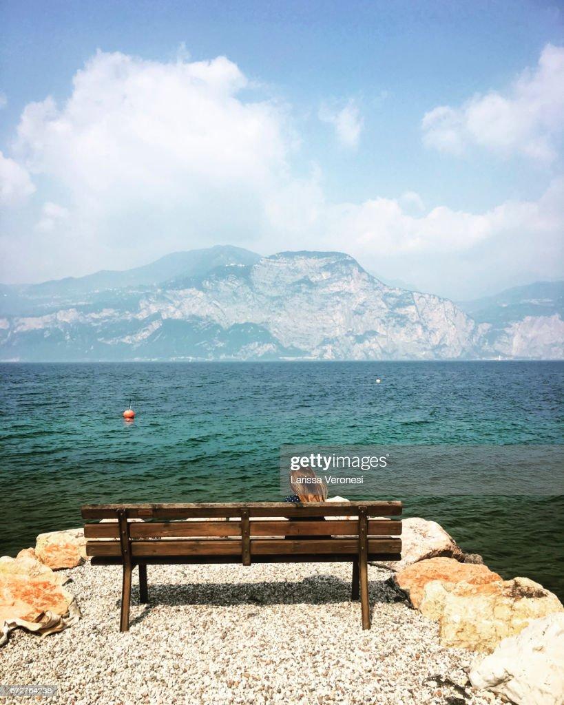 Little girl sitting on bench, Lake Garda, Brenzone Sul Garda : Stock-Foto