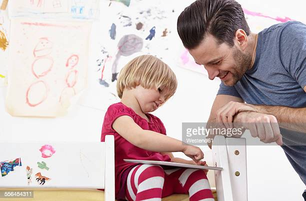 Little girl sitting on bunk bed, drawing on touch pad, father watching