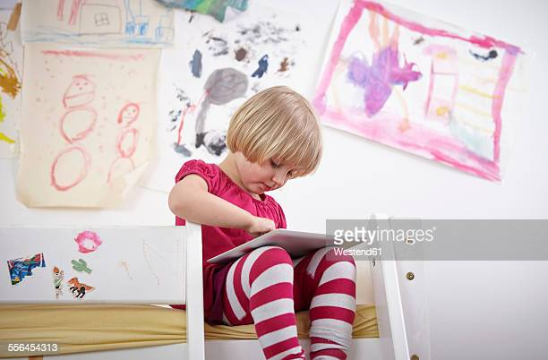 Little girl sitting on bunk bed, drawing on touch pad