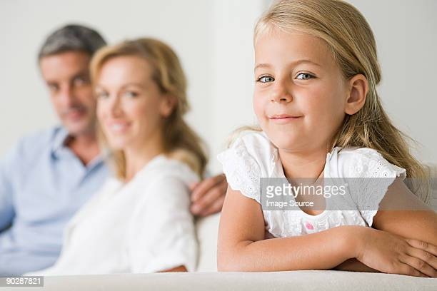 Little girl sitting on couch with her parents in background