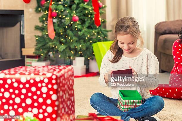 Little girl sitting on floor opening Christmas presents