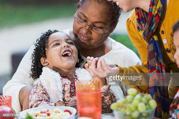Little girl sitting on grandma's lap laughing, at picnic table