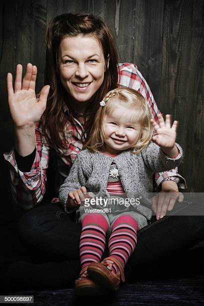 Little girl sitting on mothers lap, both are waving