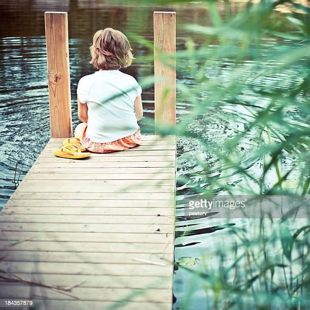 Little girl sitting on pier.