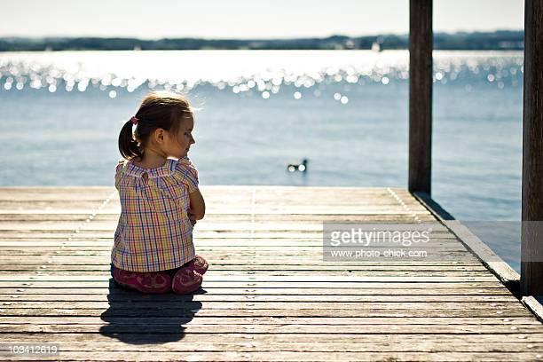 Little girl sitting on quai