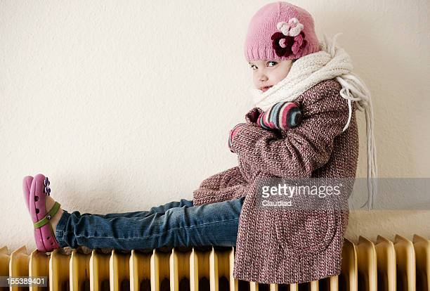 Little girl sitting on radiator