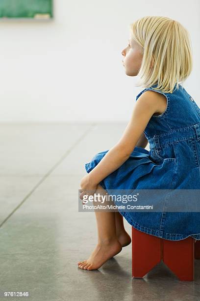 Little girl sitting on stool, looking away in thought
