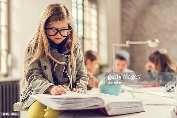 Little girl sitting on table and reading documents.
