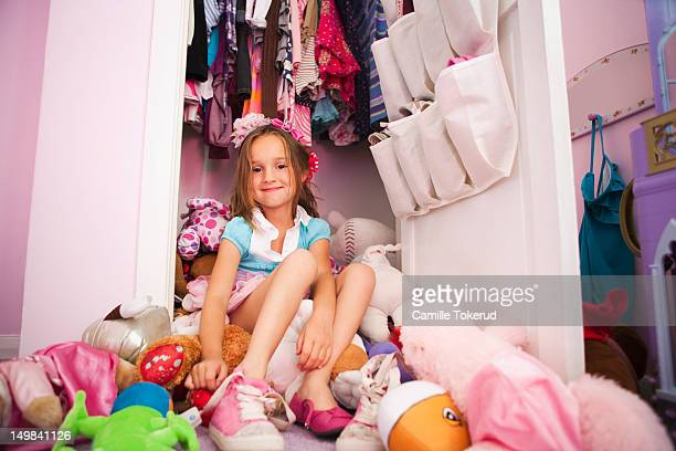 Little girl sitting on top of lots of toys