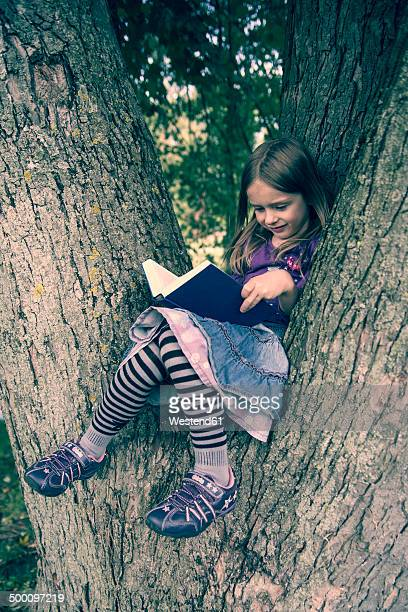Little girl sitting on tree trunk reading a book