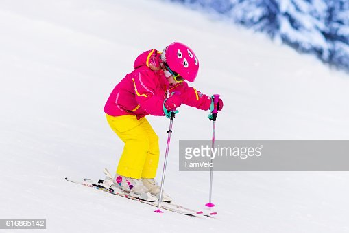 Little girl skiing in the mountains : Stock Photo