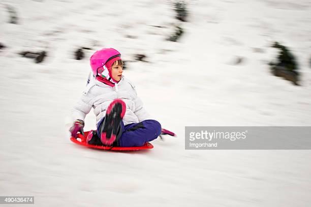 Kleines Mädchen Schlittenfahren (Schwenken