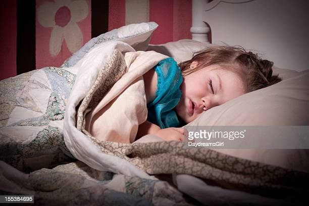 Little girl sleeping on her bed with pink wall behind her