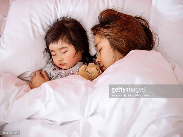 Little girl sleeping soundly in bed with mom