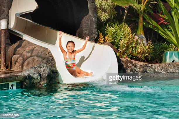 Little girl sliding down a waterslide into the pool