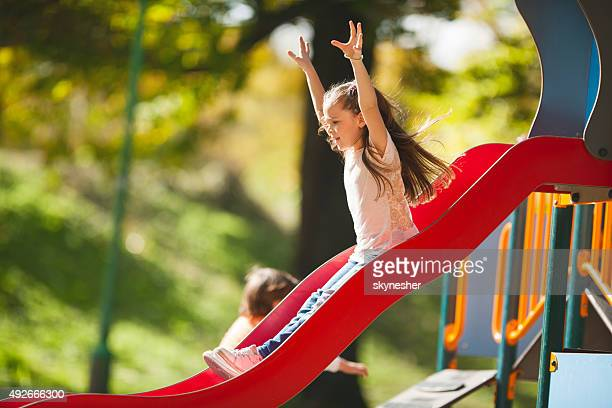 Little girl sliding with her arms raised.