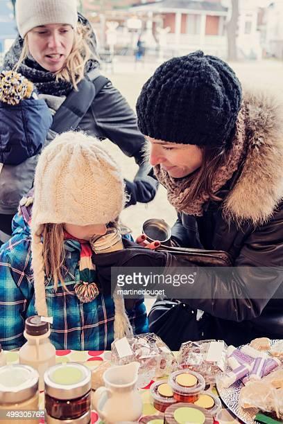 Kleines Mädchen riechen Kerze auf Outdoor-Markt im winter.