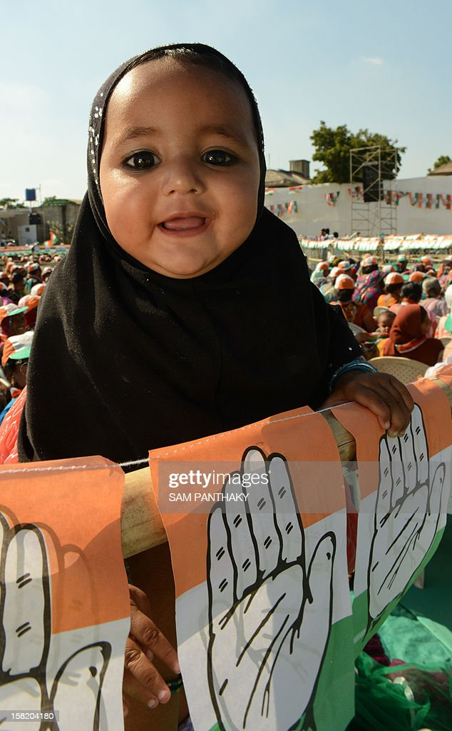 A little girl smiles during a Congress rally addressed by general secretary, Rahul Gandhi ahead of the Gujarat Assembly polls at Sanand town, some 30 kms from Ahmedabad on December 11, 2012. Gujarat state of Western India goes to polls in two phases, December 13 and 17, 2012. AFP PHOTO / Sam PANTHAKY