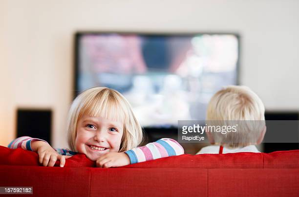 Little girl smiles while little boy watches TV