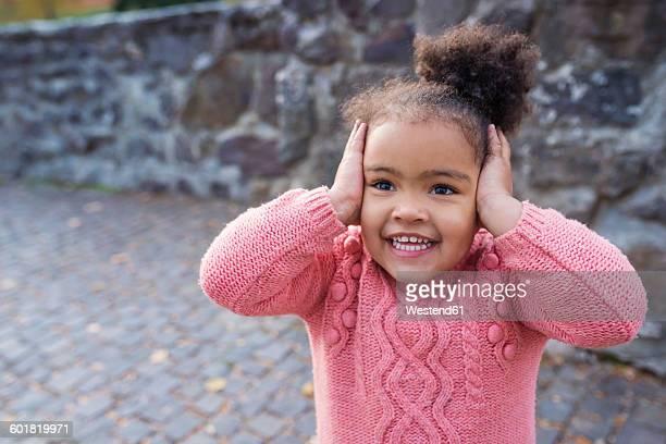 Little girl smiling, hands over ears