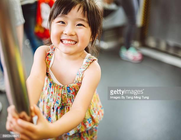 Little girl smiling joyfully in the train