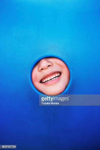 A little girl smiling through the hole