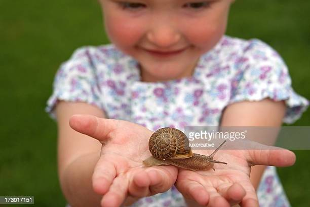 Little girl smiling while holding a snail in her hands