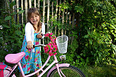 Little girl smiling while holding her bike