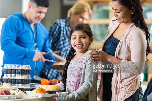 Niña sonriendo mientras reciben comida en banco de alimentos