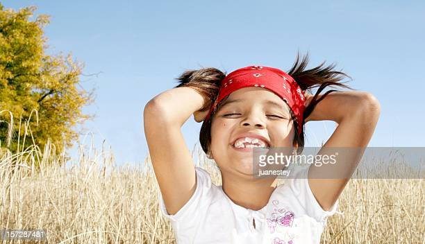 Little girl smiling with her hands in her hair over field