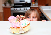 Little girl peeking over the counter while sneaking a cup cake