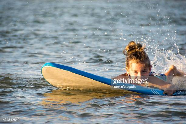 Little girl splashing around on surfboard