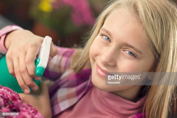 Little girl spraying flowers