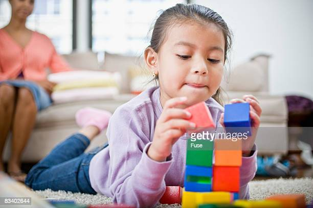 Little Girl Stacking Blocks on Floor