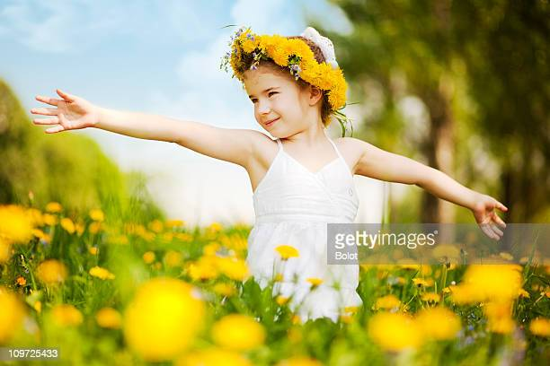 Little girl standing among dandelions with arms outstretched