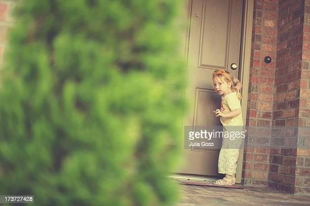 Little girl standing at front door