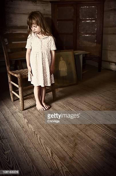Kleines Mädchen stehen in antiken Zimmer in der Nähe von Vintage Foto