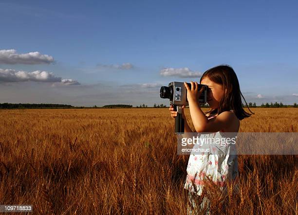 Little Girl Standing in Field and Filming with Vintage Camera