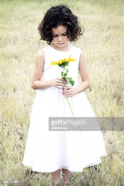 Little Girl Standing in Field and Holding Flower